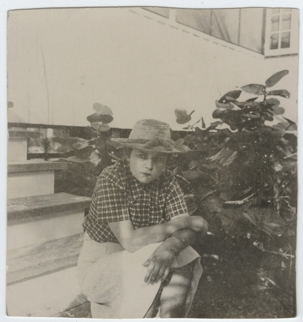 Elizabeth Bishop wearing straw hat, seated on steps.