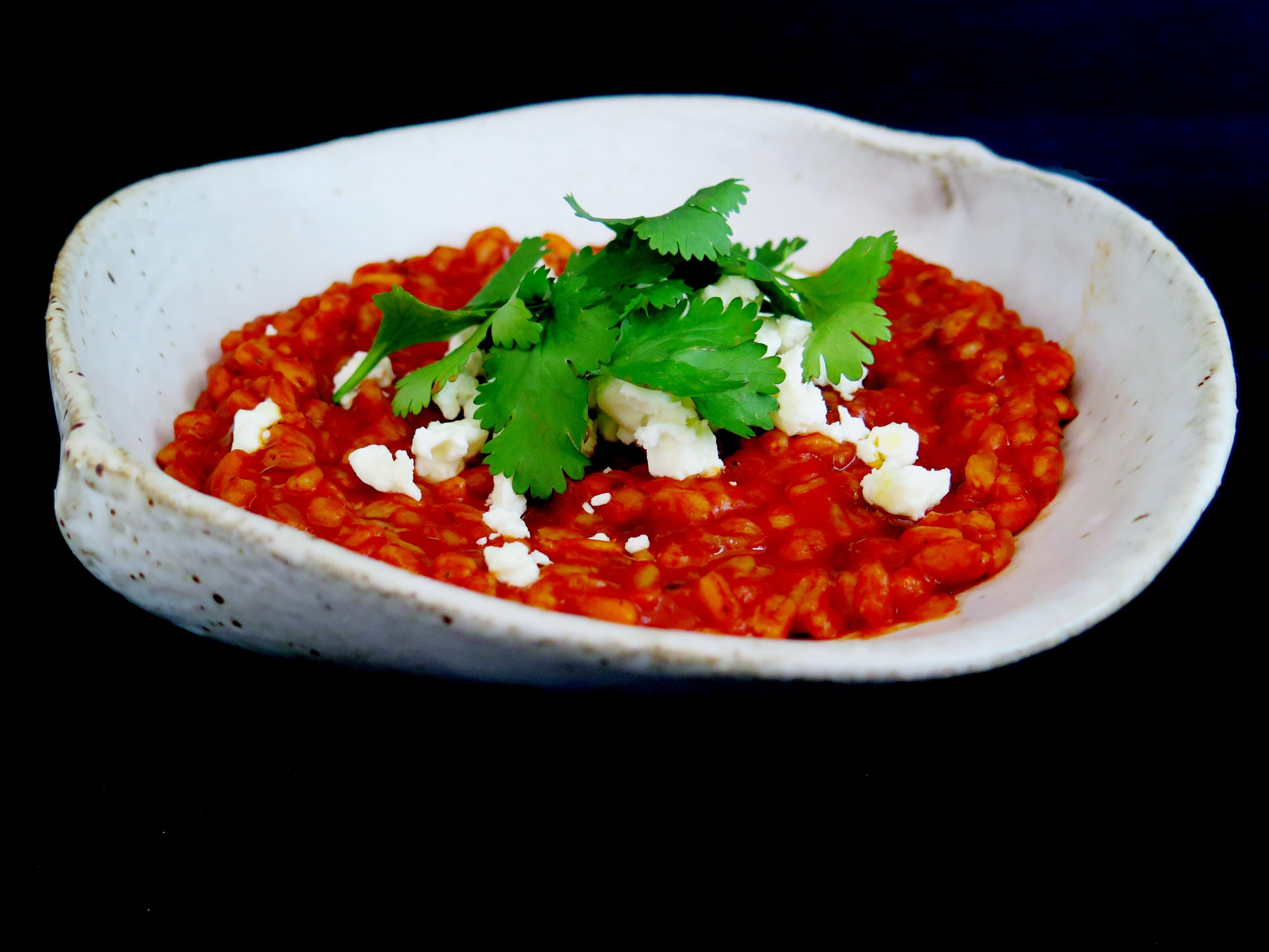 Smoky tomato and garlic spelt risotto with crumbled feta and pine nuts