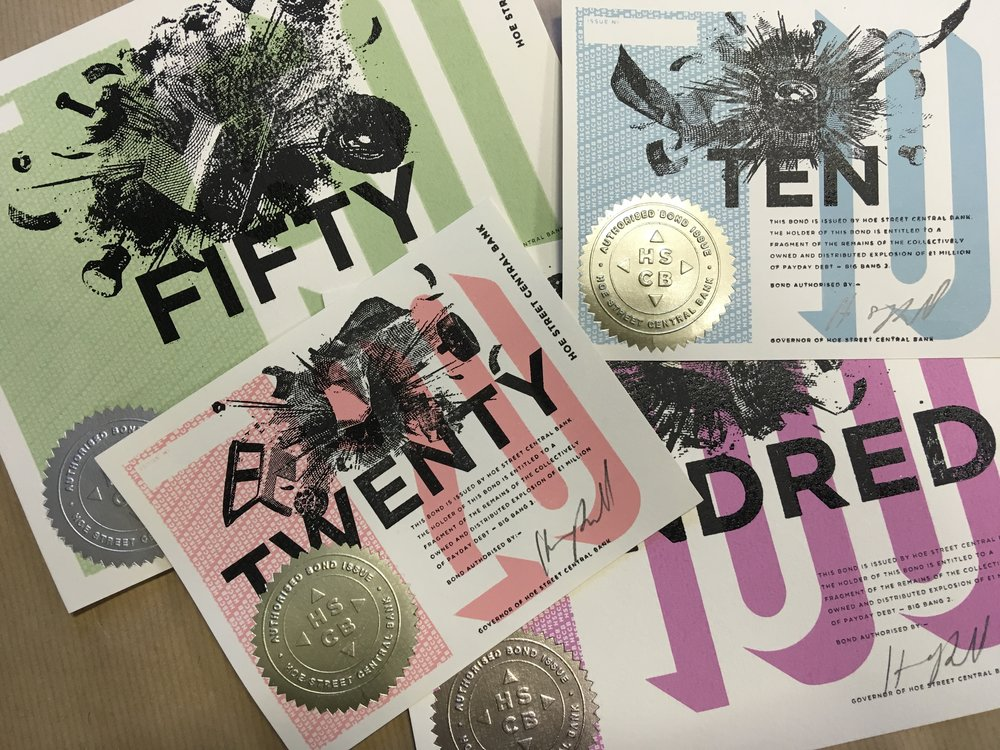 THE BONDS WERE PRINTED IN OCTOBER 2018 IN HOE STREET CENTRAL BANK BY A TEAM OF LOCAL PEOPLE WORKING WITH TRADITIONAL METHODS OF SCREEN PRINT, LETTERPRESS, FOIL BLOCK AND COMPANY STAMP.    BONDS FINANCE THE DEBT EXPLOSION - ITS FILMING, EXHIBITION, TRANSFORMATION AND DISTRIBUTION.  IT INCREASES THE IMPACT OF THIS ACT OF DEBT CANCELLATION AND QUITE LITERALLY EXPLODES THE CONVERSATION INTO PUBLIC CONSCIOUSNESS.