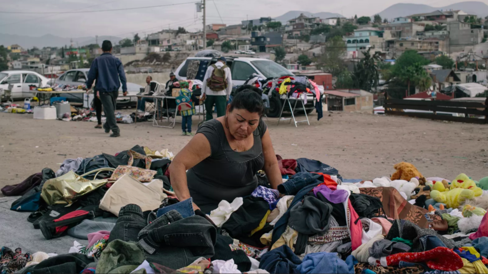 """A woman digs through used clothing at a """"market on wheels"""" in Tijuana, Mexico. Photo: Meghan Dhaliwal."""