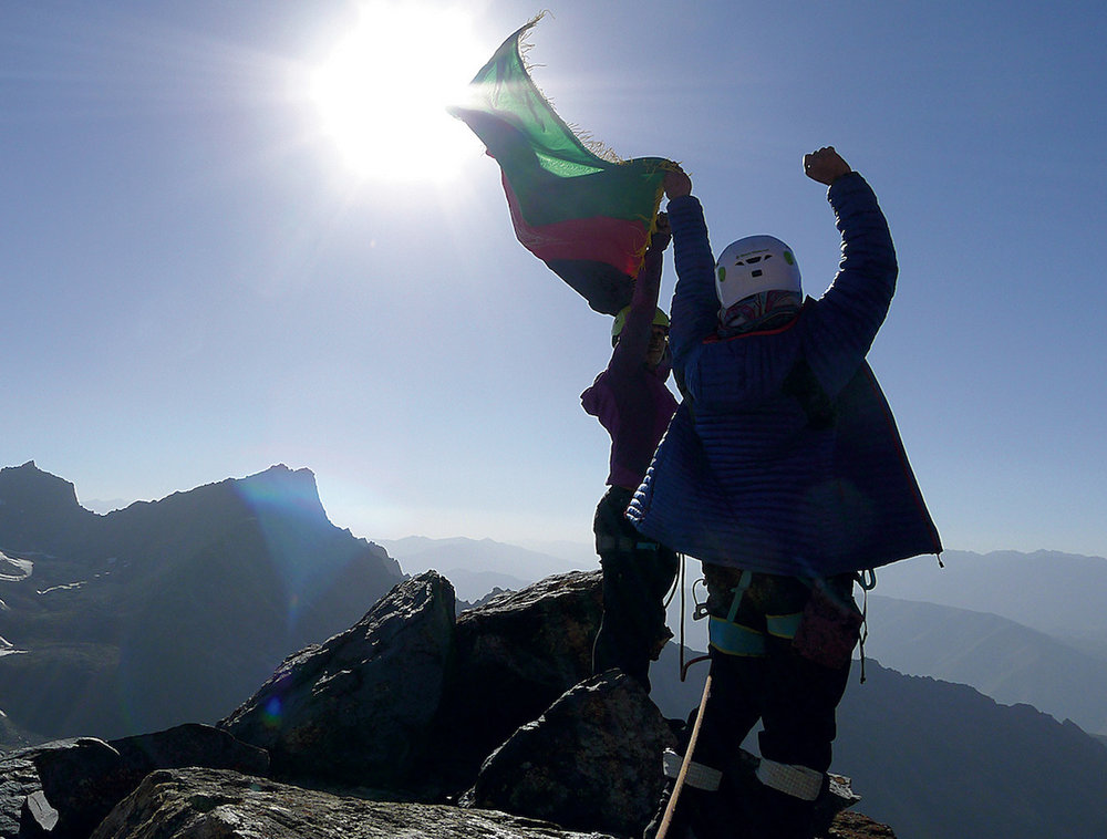 Ascend teammates Zahra and Shopirai wave the Afghan flag after completing the first ascent of a 5002-meter unnamed peak in the Panjshir mountains. Photo: Emily Drinkwater, courtesy Ascend Athletics.