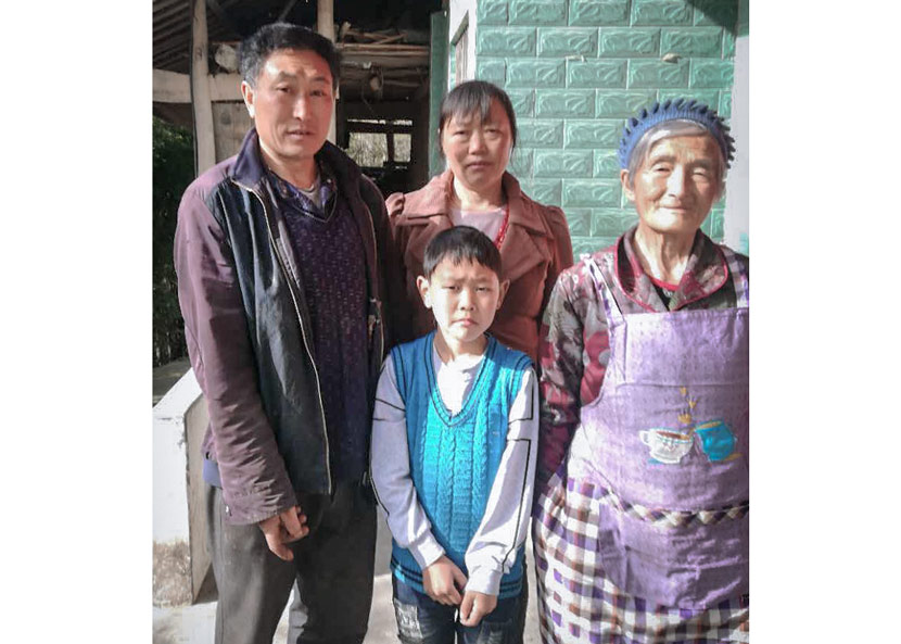 Wang Xingsun, 8, poses for a photo with his parents and grandmother outside their home in the mountains above Piankou Township, Sichuan province, April 2018. Xingsun hopes to become a scientist, but his aging parents worry about how they will pay for his schooling. Courtesy of the Wang family