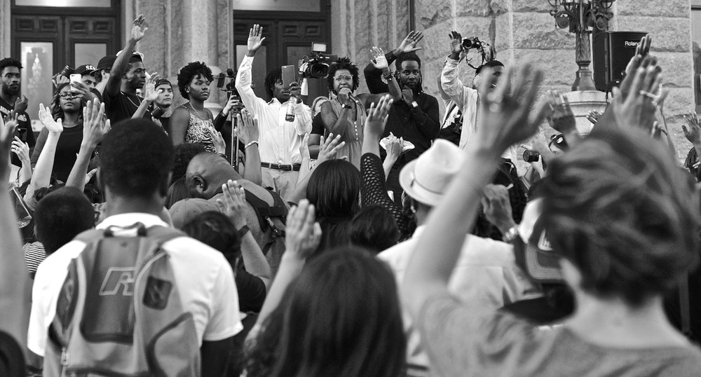 From left to right, center of photo, Michael Junior (upraised hand, white shirt), Fatima Mann and Nijalon Dunn exhort the crowd during the July 15, 2016, Black Lives Matter rally at the Texas Capitol in Austin.