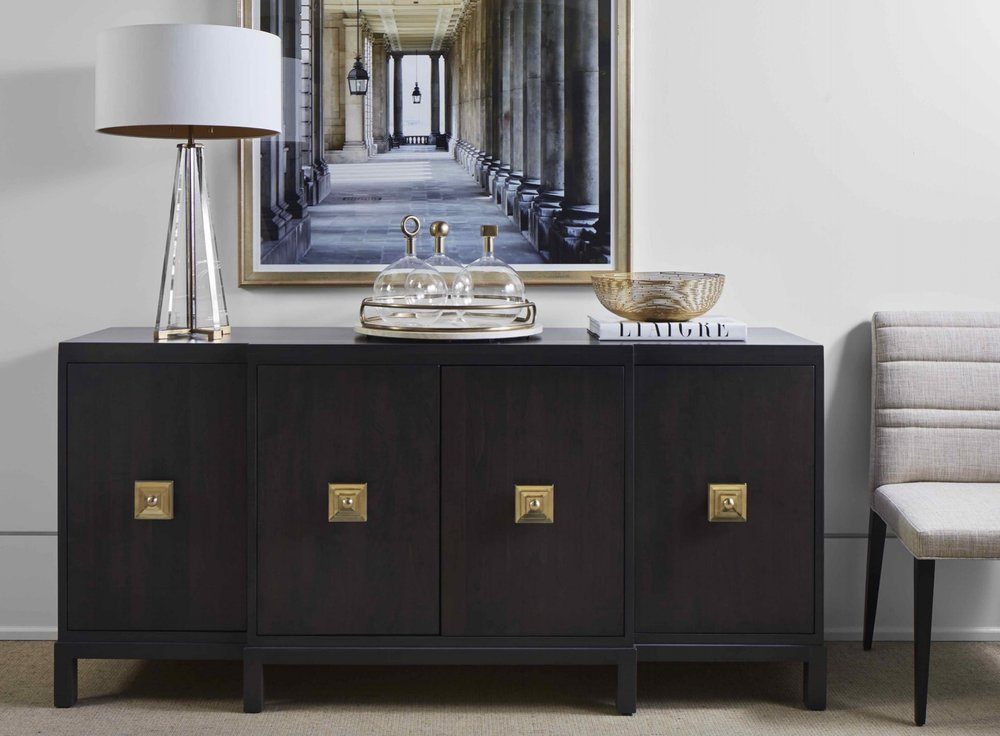 A buffet with stepped front, block legs, deep rich stain and showstopping brass hardware.