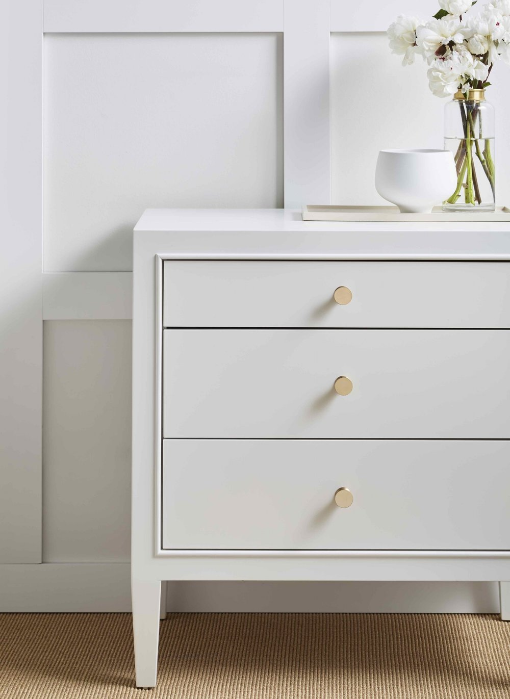 Three-drawer nightstand with bead moulding detail to frame drawers. Paint finish in Chantilly Lace by Benjamin Moore.