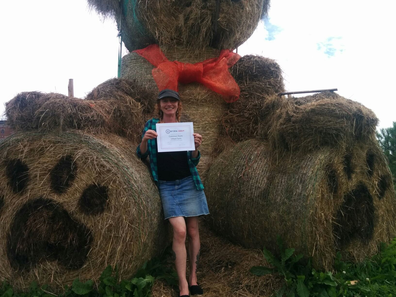Jayme Melrose standing under the Hay Bear at Common Roots Urban Farm, and holding her new Buy Social Canada certification!