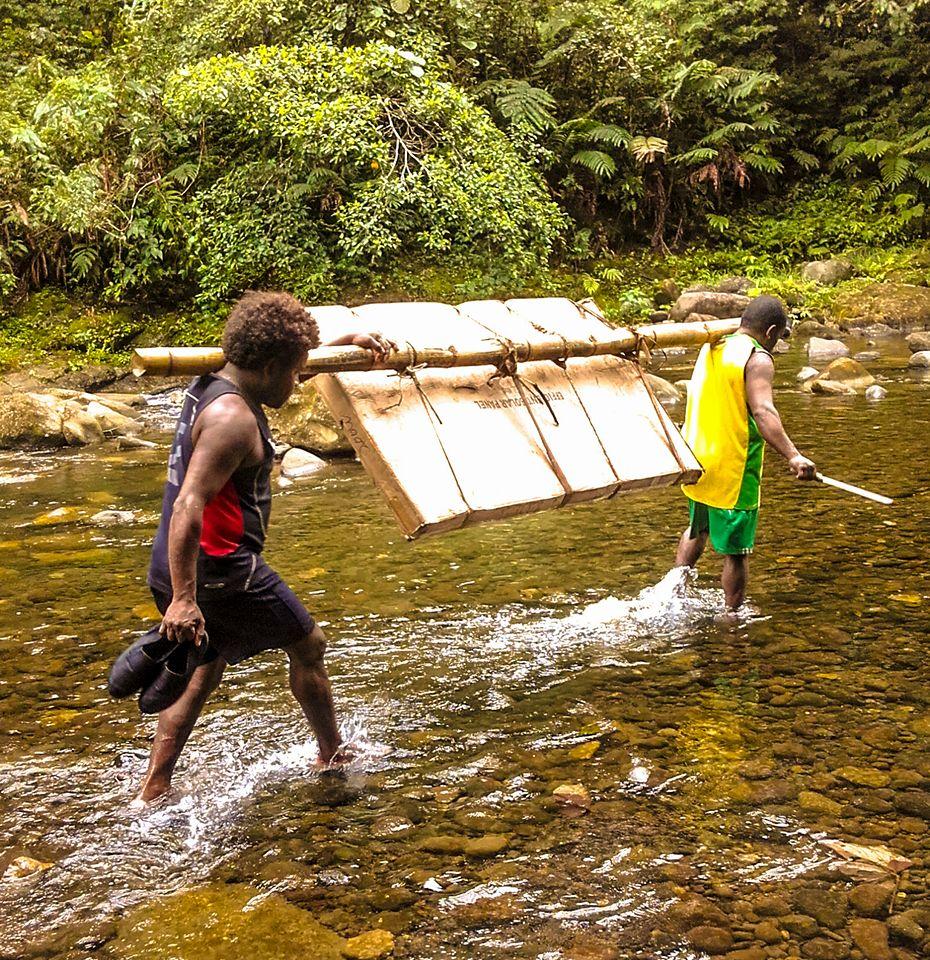 Two Vanuatuan men carry the solar panel across the river