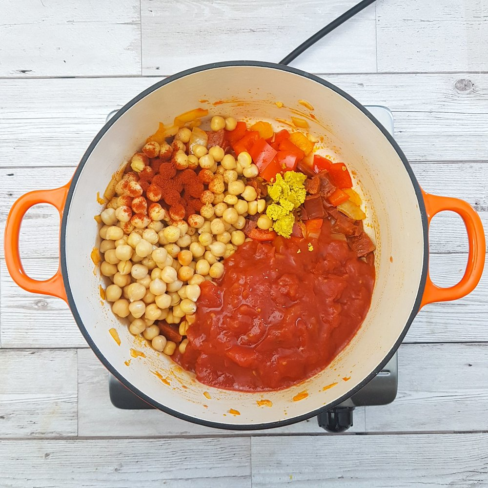 Drain the chickpeas and add to the vegetables, along with 2 tsp smoked paprika, the chopped tomatoes, and a chicken stock cube. Stir well, place a lid on and cook over a medium-heat for 12 minutes