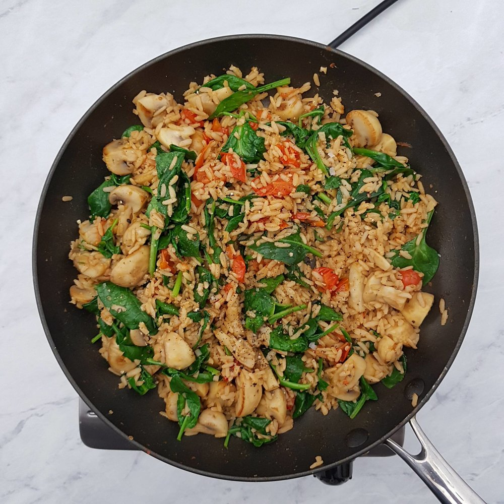 Add the spinach. Stir together until the spinach is wilted, then add the remaining tomatoes. Divide the rice between to plates then cook the halloumi.