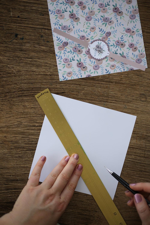 2. Vi börjar med att göra locket. Vänd på arket och markera en mittpunkt, genom att lägga en linjal som diagonal och gör ett streck. Gör en diagonalmarkering genom de andra hörnen också.