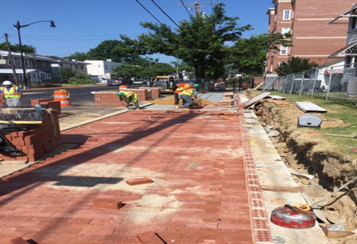 Brick sidewalk on PCC base installation at 9th & Kennedy Street brick retaining wall