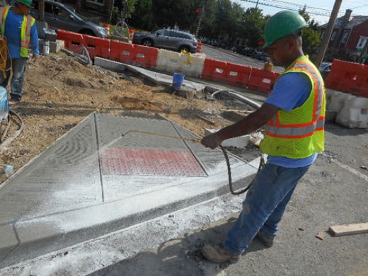 Workers spraying cured Concrete on ADA ramp at Missouri Kennedy and Kansas intersection