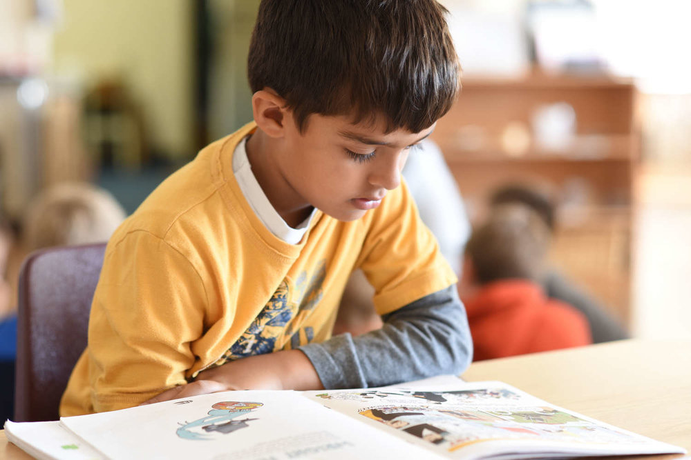 Boy reading a book in class as part of the Montessori method of learning