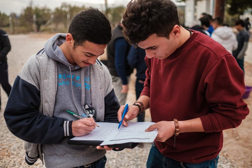 Mohamad and Ferhad fill out questionnaires in Arabic and English.
