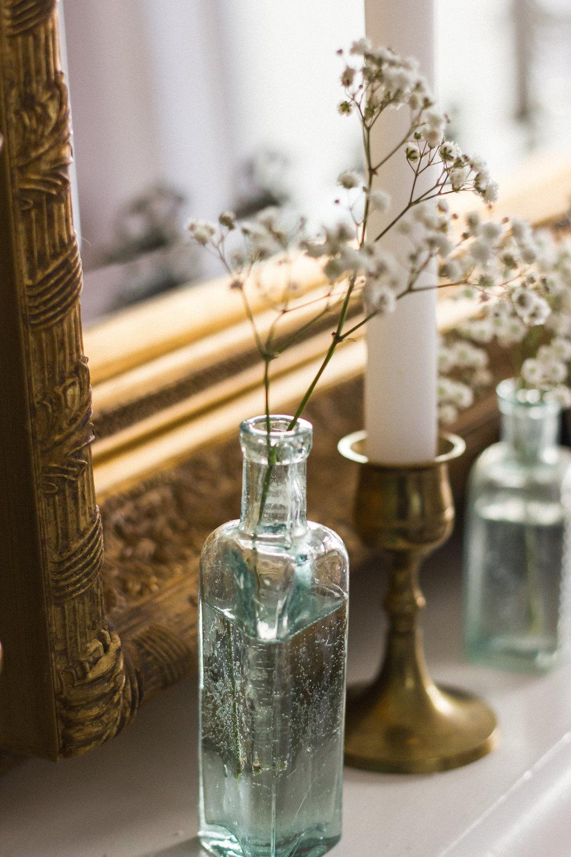 Vintage medicine bottles and vintage brass candlesticks are a perfect combination for an elegant vintage wedding.
