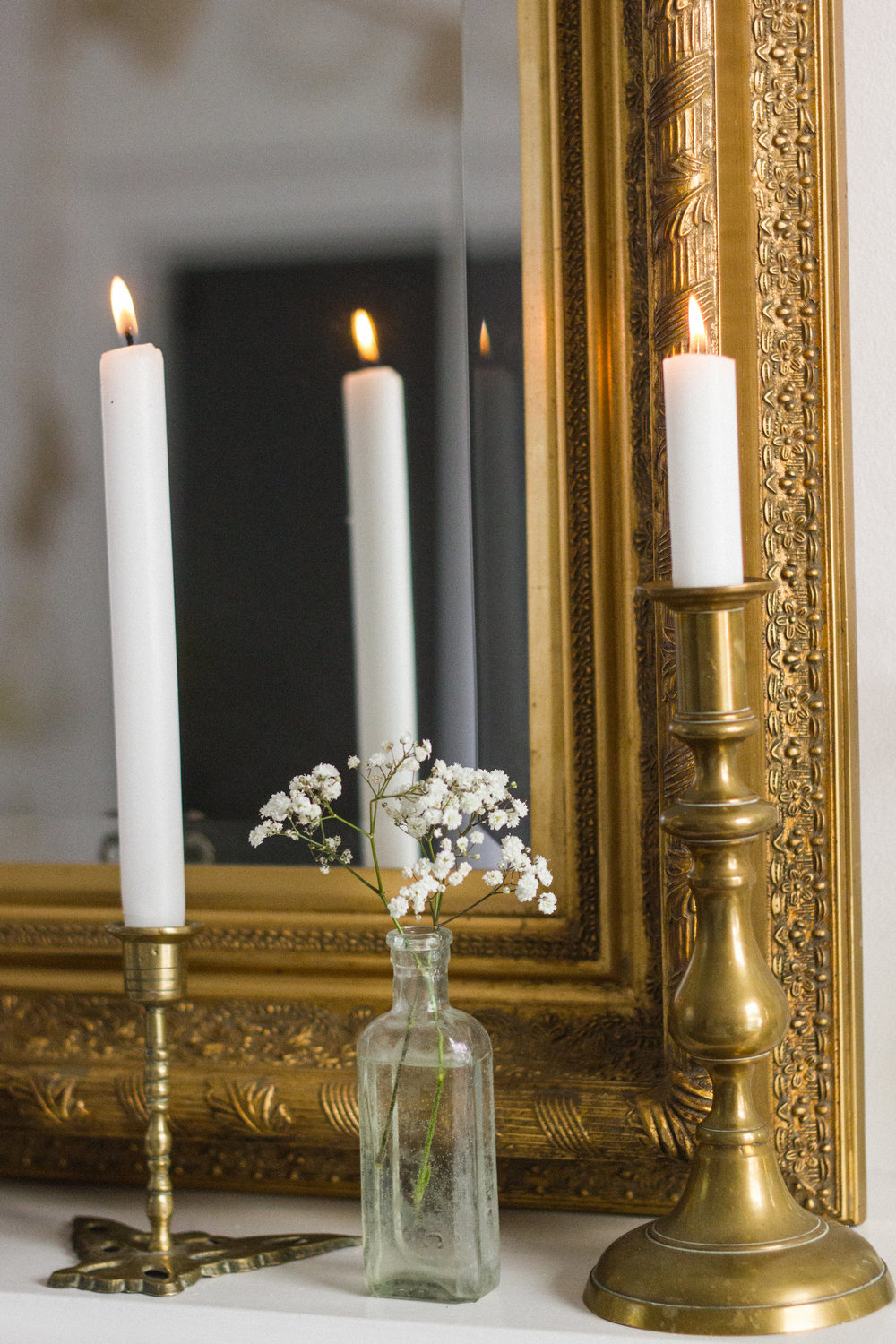 The brass of these vintage candlesticks works perfectly with the brass mirror.