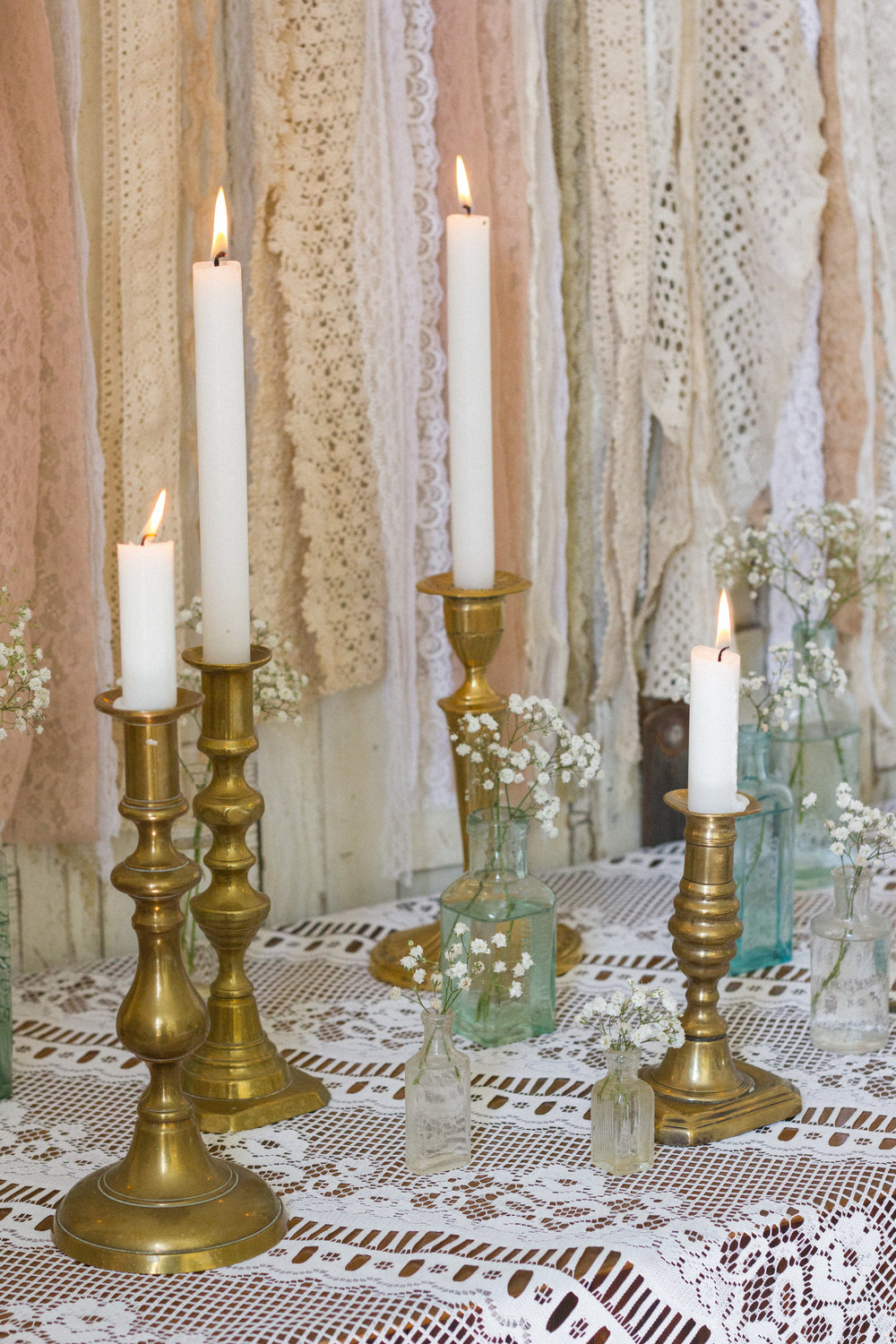 Brass candlesticks on lace is so pretty.