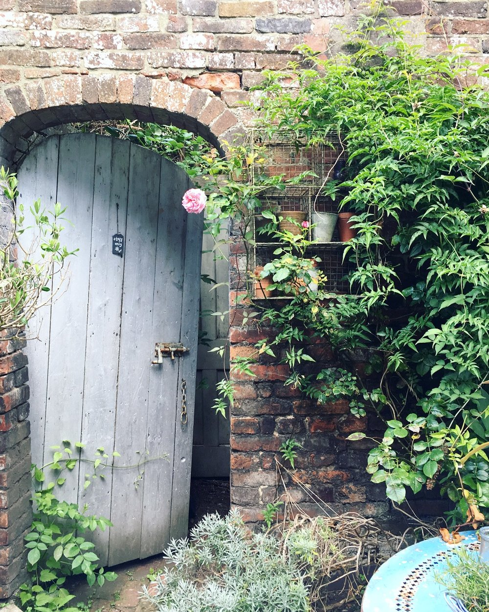 The gorgeous  Closet & Botts  in Lewes, East Sussex has a lovely courtyard with my favourite - an old wooden door in a brick wall!