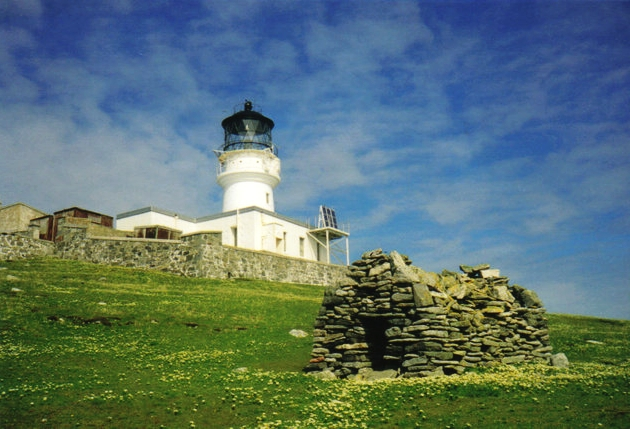 The lighthouse with the stone chapel built by  St. Flannan  in the 7th century in the foreground.   Photo Credit  By JJM, CC BY-SA 2.0
