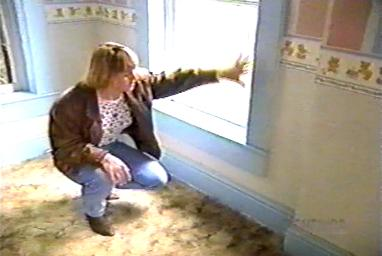 A woman who lived at the Sallie House as a young girl, after the Pickmans, pointing to a spot near a window in the nursery where she saw fire spontaneously appear
