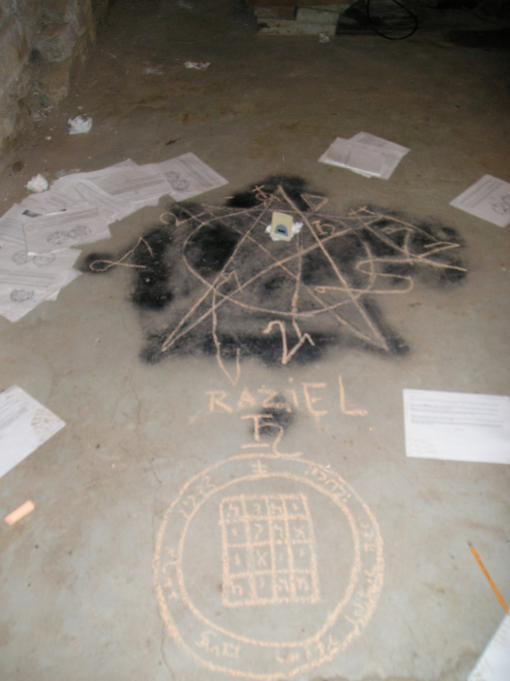 A demonologist's attempt at retracing the pentagram that was left on the floor of the basement by a previous tenant, in order to determine what spells had been cast, and then adding some protective sigils in its place.