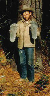 """Roger Patterson shown with two plaster castings he took of """"Patty's"""" footprints at the Bluff Creek encounter site."""