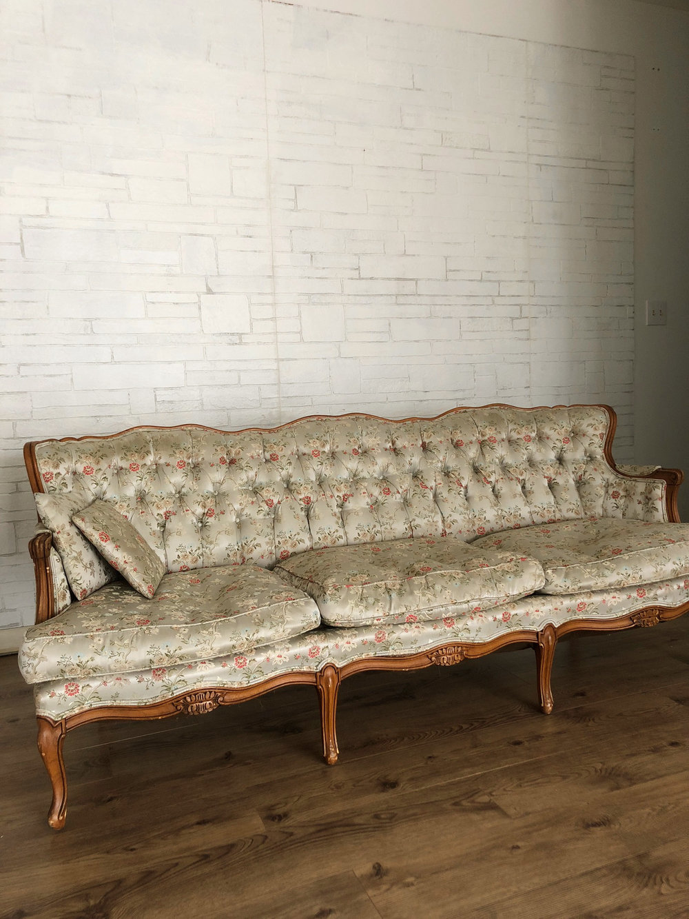 extra long  antique sofa - white brick backdrop