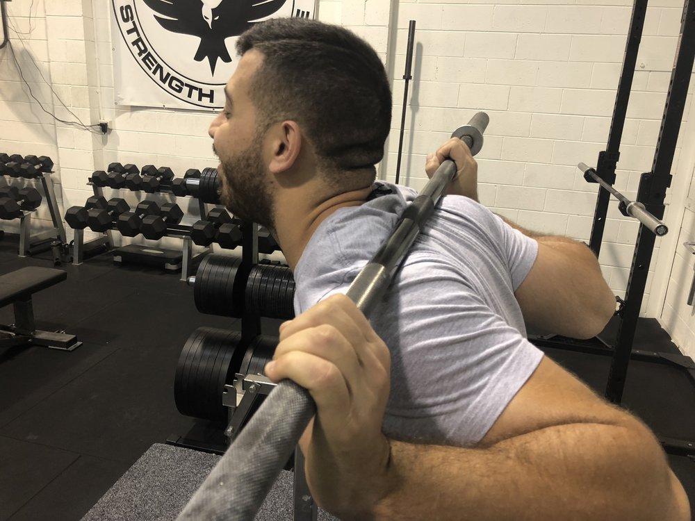 A poor Low Bar Position - scapulae anteriorly tilted, neck and wrists extended, elbows flared