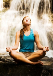 Woman in Lotus Position by Waterfall