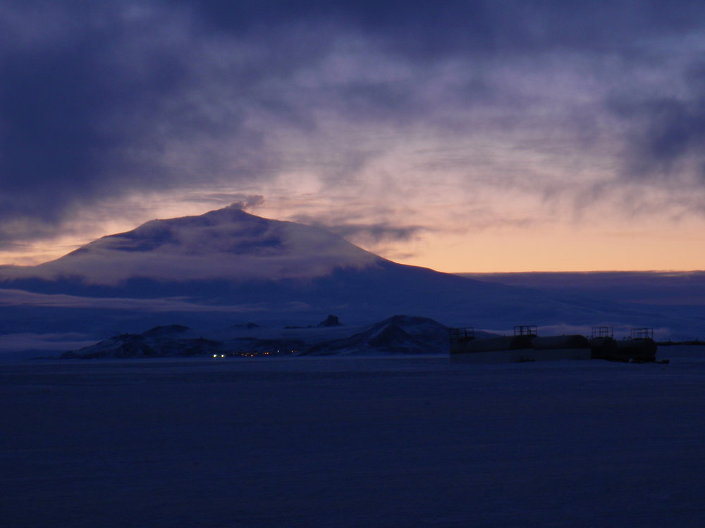 A view of Ross Island from Pegasus Field, during one of the long twilights. Mount Erebus looms in the background over the lights of McMurdo Station. In the foreground are fuel tanks for the airfield.  Photo curtesy of Alan R Right, wikimedia