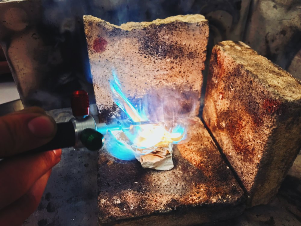 Brass is mostly copper, and the blue flames are a sure sign that it's burning.