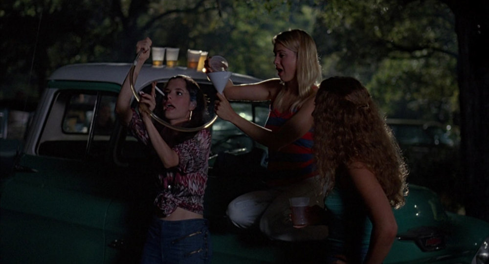 """Darla (Parker Posey) gets ready to drink from a """" beer bong """" as a fellow student (an uncredited  Renée Zellweger ) pours the beer during the """"Party at the Moontower"""" © 1993 Universal City Studios, Inc."""