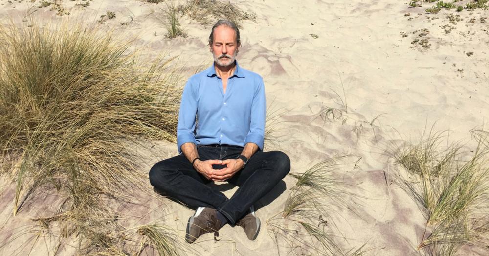 Anthony Thompson meditating on a beach