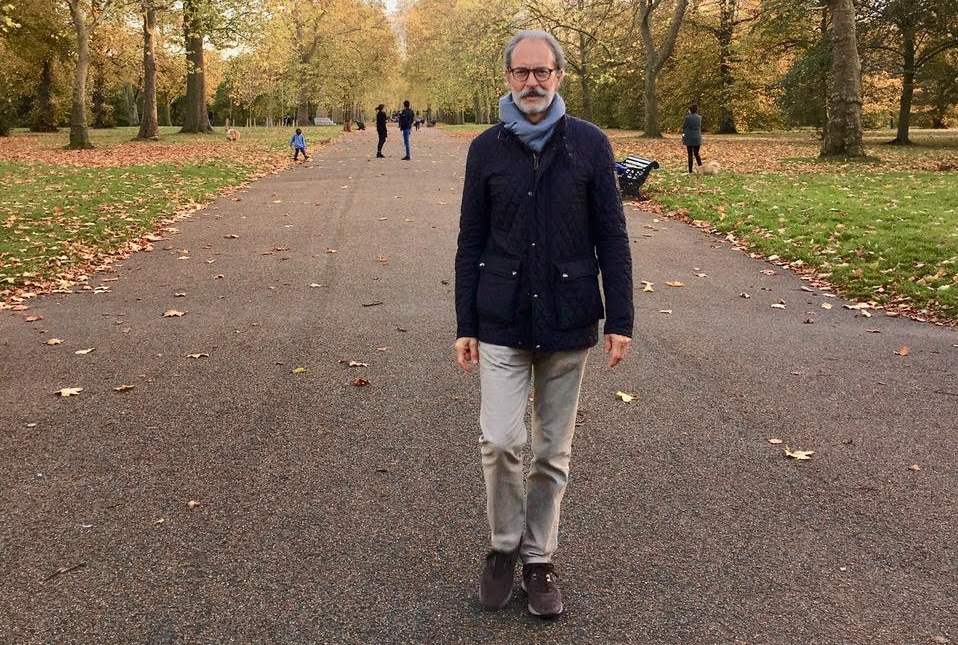 Anthony walking through a park in Autumn