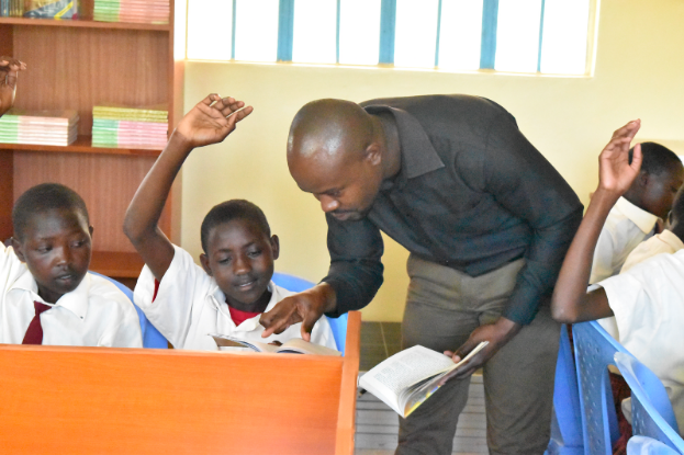 English teacher Mr. Okello helps one of his 7th grade students in the library.