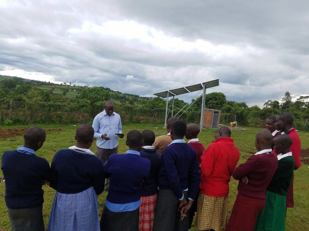 Headteacher Daniel Kishoyian greets the girls outside on their first day. Some of the school's solar panels can be seen in the back right.