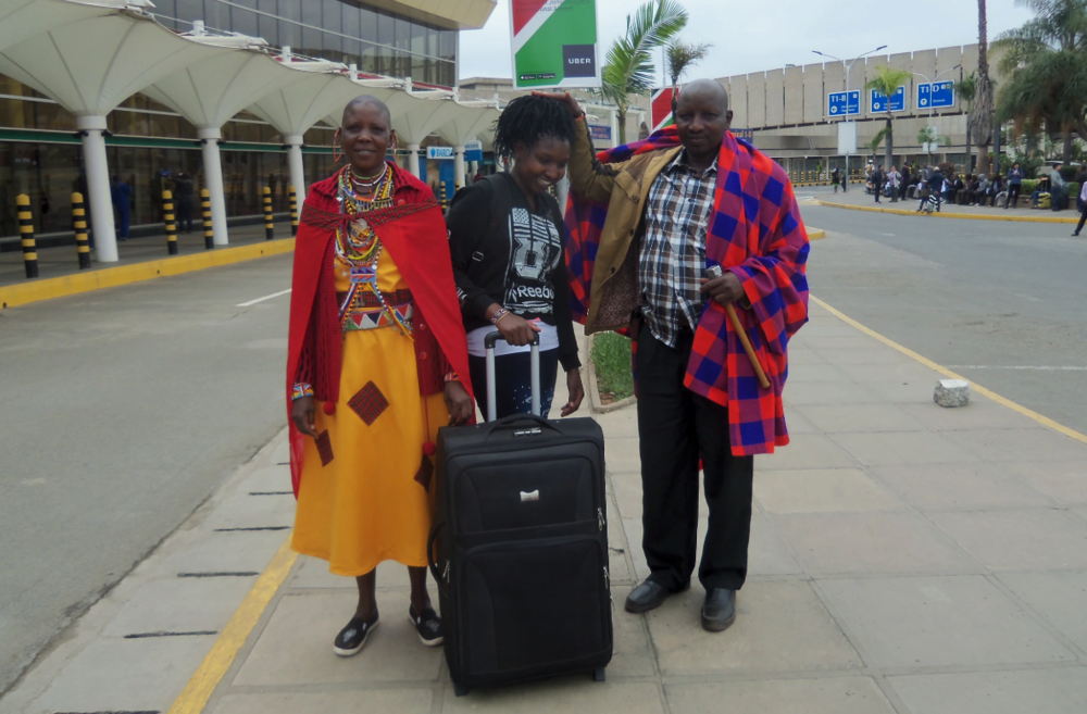 Magdalene says goodbye to her parents. Her father gives her a traditional Maasai blessing by placing his hand on her head.