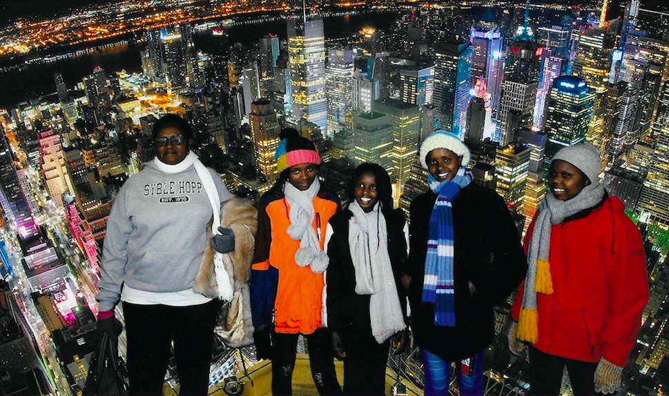 The girls pose with their head teacher for a photo at the Empire State Building