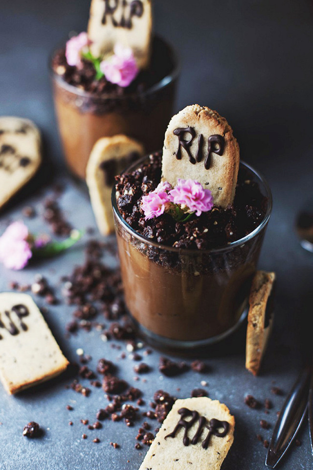 NAKD GRAVEYARD MOUSSE POTS!  PREP TIME:15 mins  COOK TIME:8 mins  TOTAL TIME:23 mins  Lemon poppyseed tombstone cookies paired with velvety chocolate mousse with a Nakd bar crumble topping. A deliciously spooky dessert perfect for Halloween!  Serves:4  INGREDIENTS:  For the chocolate mousse pots   Nakd mousse pots recipe   For the tombstone cookies  175g / 1¾ cup ground almonds  1 tbsp arrowroot powder  2 tbsp coconut oil  2 tbsp agave nectar  1 tbsp vanilla extract  Zest of 1 medium lemon  1 tbsp poppy seeds  For the chocolate icing  2 tbsp coconut oil  2 tbsp cocoa powder  1 tbsp agave nectar  1 tsp vanilla extract  INSTRUCTIONS:Make the mousse pots according to  these instructions . You can make two large servings or four small pots. Leave in the refrigerator whilst you prepare the cookies.  To make the cookies:Preheat the oven to 180c / 350f and line a baking tray with parchment paper.In a food processor or mixer, mix together the ground almonds and arrowroot powder. Add the coconut oil in a small bit at a time so it's evenly distributed throughout the dough.Mix in the rest of the ingredients and turn the dough out onto a board.Roll the dough so it's about ¼ inch thick and using a small sharp knife, cut out your tombstone shapes. Or , if you have tombstone cookie cutters, even better!  Transfer to the baking sheet and bake for 5-8 minutes until golden brown around the edges. Leave to cool before icing.  To make the icing:Melt the coconut oil over a bowl of hot water. Stir in the cocoa powder, agave and vanilla extract. Leave to cool in the fridge for a few minutes.  Transfer the chocolate to an icing bag with a narrow nozzle, suitable for writing. Test a small amount to see if the icing is too runny. If so, return to the fridge to firm up slightly. Once it's the perfect texture, pipe your RIP letters onto the top of the tombstone cookies and leave to set in the fridge for at least 10 minutes.  To assemble:Stand the tombstone cookies on top of your mousse pots.  