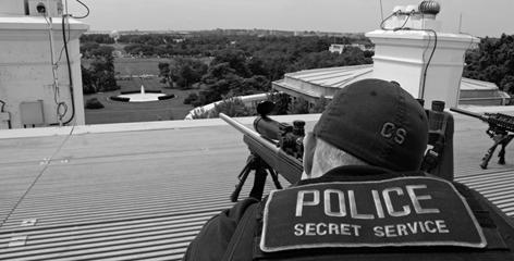 """A U.S. Secret Service """"counter-sniper"""" marksman on top of the White House's roof, armed with a sniper rifle."""