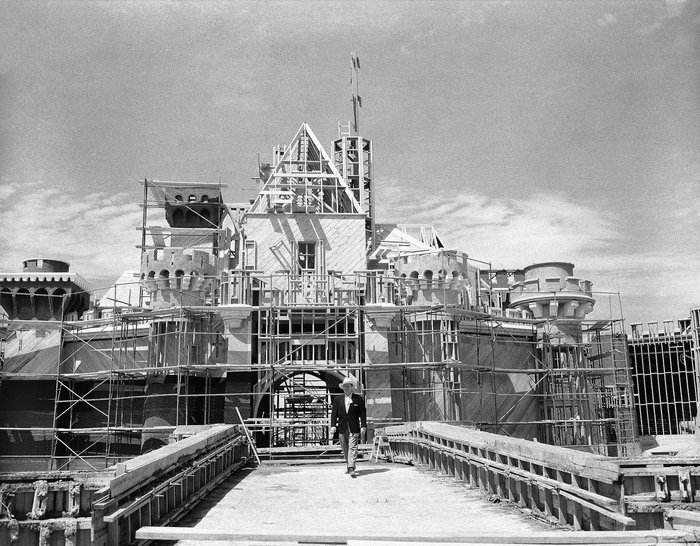 Walt Disney walks on the bridge in front of the partially finished Sleeping Beauty's Castle at Disneyland. Credit: AP Images