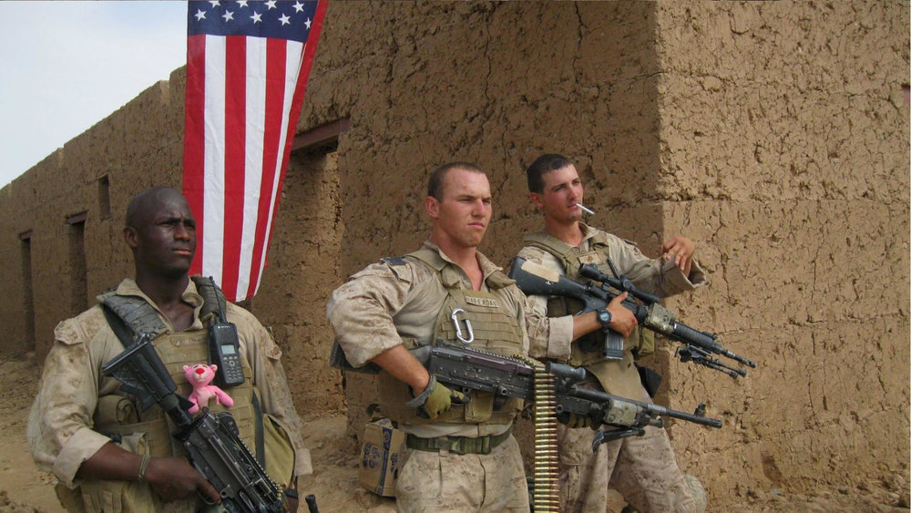 Cpl. Kionte Storey (left) with American Flag