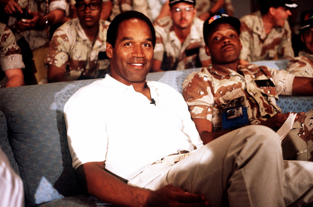 NBC Sports commentator and former professional football player O. J. Simpson sits with a group of servicemen to watch a Thanksgiving Day football game. Simpson is visiting U.S. troops who are in the region for Operation Desert Shield. November 22, 1990.