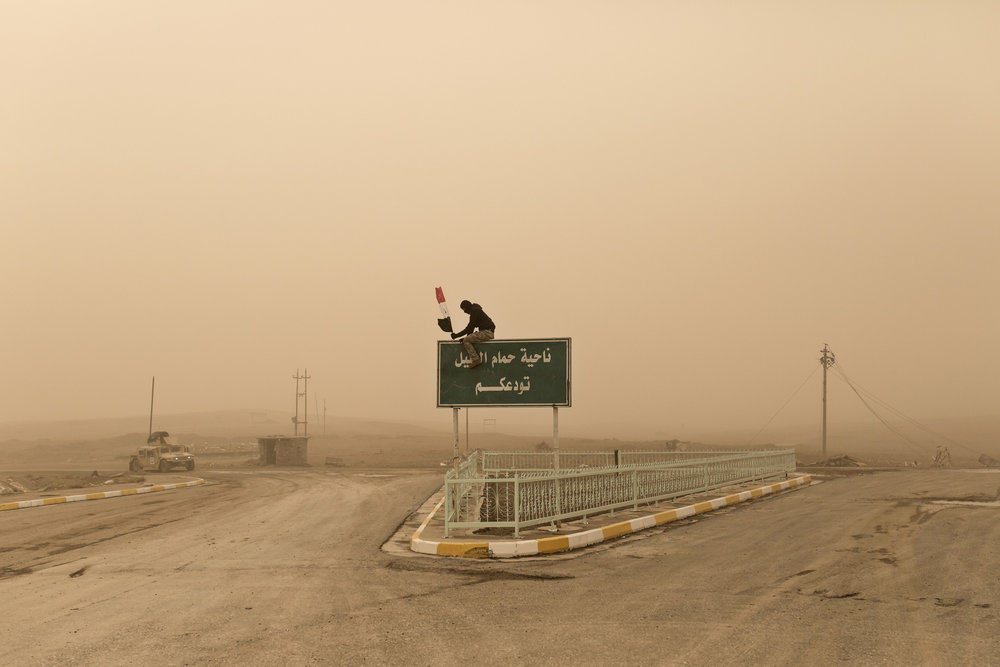 An Iraqi Federal Policeman fixes an Iraqi flag to a road sign outside the town of Hammam al Alil.
