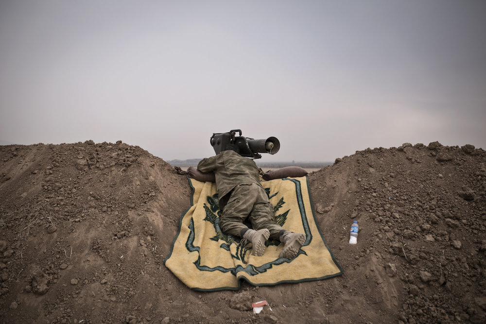 A Kurdish soldier watches an Islamic State held village through the scope of a German anti-tank weapon.