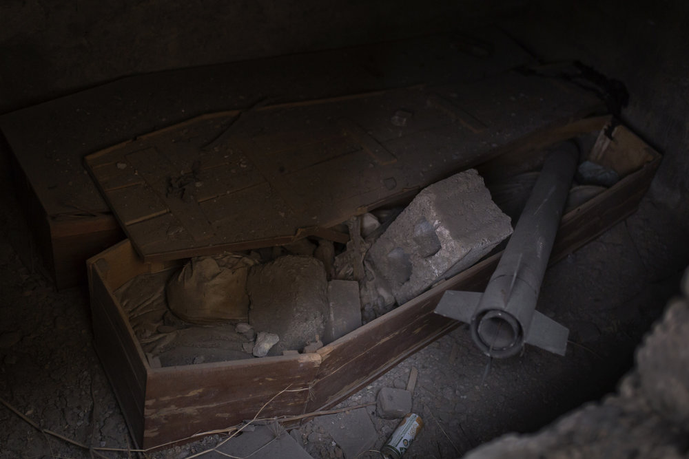 A looted tomb in a church in Bartella containing an opened coffin and an unexploded rocket.