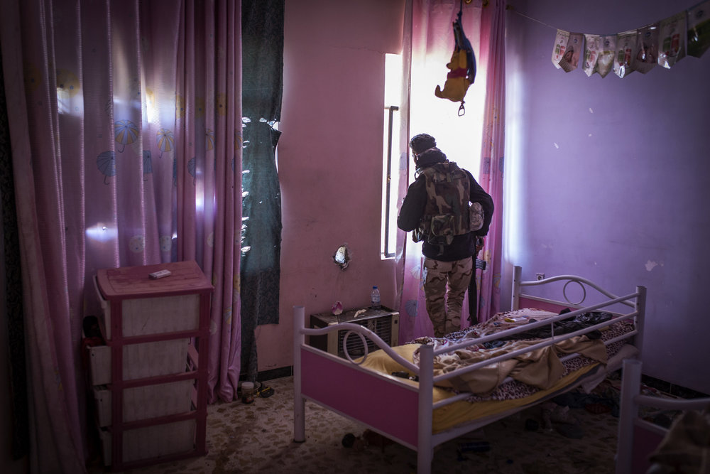 An Iraqi soldier peers through the window of a child's bedroom during clashes with Islamic State forces in Mosul.