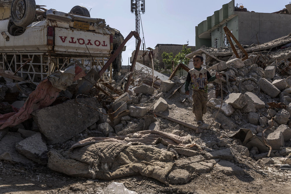 A child crosses rubble in Mosul near the covered corpse of an Islamic State militant.