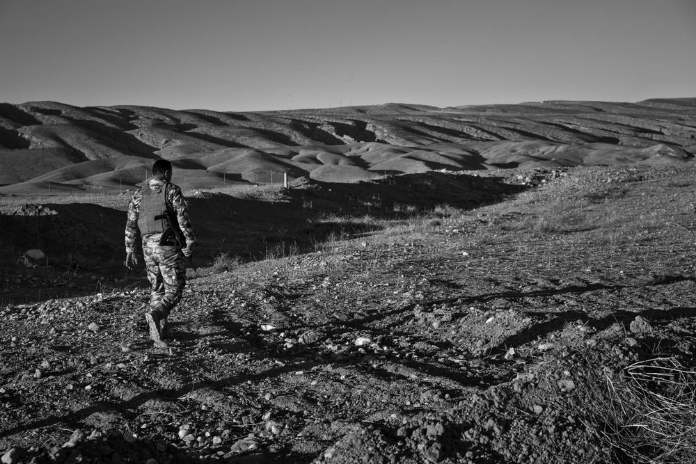 A Kurdish Peshmerga walks through the site of a mass grave in Sinjar.