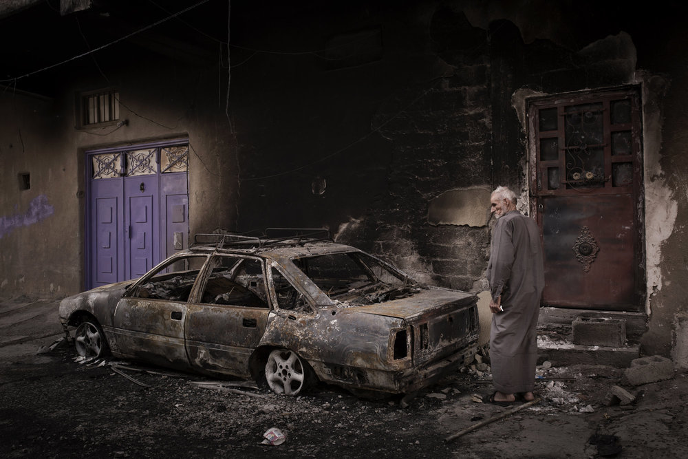 An elderly resident surveys damage outside his property after it was looted and burnt.